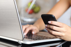Mano de la mujer usando un teléfono elegante y mecanografiar un ordenador portátil en casa