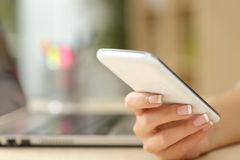 Mano de la mujer usando un teléfono elegante blanco Fotos de archivo libres de regalías