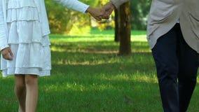 Mano de la niña de la tenencia de la mujer y el caminar en parque verde en el verano, fin de semana almacen de metraje de vídeo