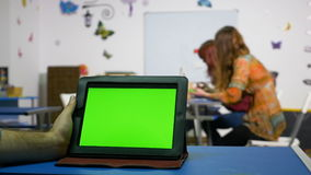 Mano de la PC de la tableta de la tenencia del hombre con la pantalla verde en un cuarto del curso almacen de metraje de vídeo