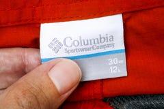 Mano de la persona con la etiqueta de la ropa de la compañía de Columbia Sportswear imágenes de archivo libres de regalías