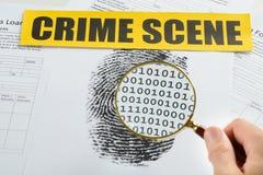 Mano de la persona con la lupa y la cinta de la escena del crimen Foto de archivo