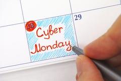 Mano de la persona con la pluma que escribe lunes cibernético en calendario Fotografía de archivo libre de regalías