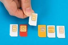 Mano de la persona con las tarjetas del sim Fotos de archivo