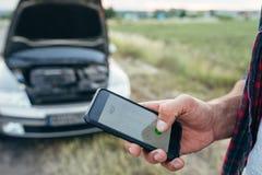 Mano de la persona masculina con el teléfono, coche roto fotografía de archivo libre de regalías