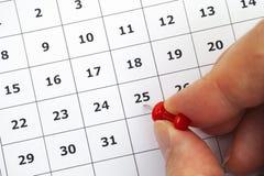 Mano de la persona que pone el perno en el número 25 en calendario Imagen de archivo libre de regalías