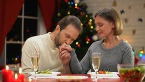 Mano de la señora del hombre que se besa cuidadosamente, teniendo fecha romántica el la víspera de Navidad, par cariñoso almacen de metraje de vídeo