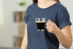 Mano de la señora que sostiene una taza de café en casa Fotos de archivo