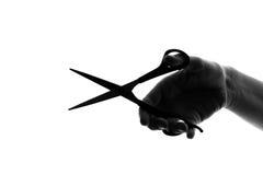 Mano de la silueta con las tijeras del corte Fotografía de archivo