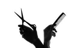 Mano de la silueta con un peine y las tijeras Fotos de archivo libres de regalías