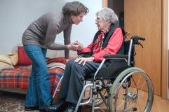 Mano de la tenencia de la mujer joven de la mujer mayor triste con la silla de ruedas imagenes de archivo