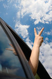 Mano de la ventana del coche. símbolo de la victoria Foto de archivo libre de regalías