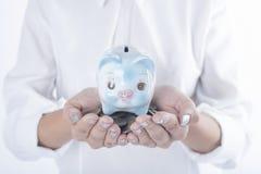 Mano de las mujeres de negocios que sostiene la moneda y la hucha ahorro del concepto imagen de archivo libre de regalías