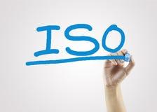 Mano de las mujeres que escribe el ISO en el fondo gris para la estrategia empresarial Imágenes de archivo libres de regalías