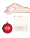 Mano de las mujeres que sostiene la bola roja del Navidad-árbol Fotos de archivo