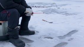 Mano de los pescados de las capturas del pescador en la caña de pescar del invierno en el río congelado con el agujero almacen de metraje de vídeo