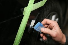 Mano de los spackles del trabajador del servicio del coche una pequeña abolladura en el tope del coche foto de archivo libre de regalías