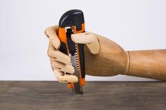 Mano de madera con el cuchillo de corte de la oficina fotos de archivo