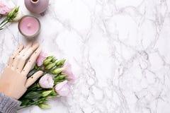 Mano de madera con las flores rosadas en el fondo de mármol imagen de archivo libre de regalías