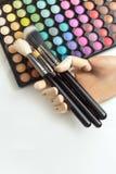 Mano de madera con los cepillos del maquillaje, maquillaje colorido del maniquí en blanco Foto de archivo