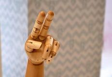 Mano de madera de la muñeca que muestra dos fingeres Imágenes de archivo libres de regalías