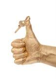 Mano de oro con un clave imagen de archivo