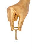 Mano de oro con un clave sobre blanco foto de archivo libre de regalías
