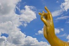 Mano de oro de la estatua de Guanyin con la nube y el cielo azul Imagenes de archivo