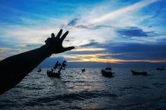 Mano de Silhiuette grapping con la playa en la puesta del sol Foto de archivo