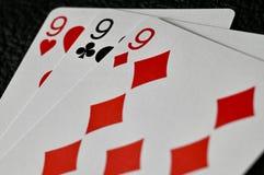 Mano de 999 tarjetas en fondo texturizado negro imagen de archivo