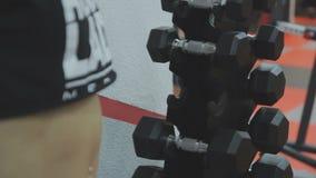 Mano de tomar de las mujeres jovenes pesas de gimnasia en el gimnasio metrajes