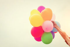 Mano de un adolescente que sostiene los globos coloridos en la sol Imagen de archivo
