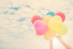 Mano de un adolescente que sostiene los globos coloridos en la sol Fotografía de archivo libre de regalías