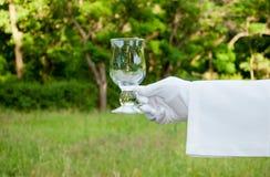 Mano de un camarero en un guante blanco que sostiene un vidrio de agua en el aire abierto Imagen de archivo libre de regalías