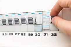Mano de un electricista que gira un fusible Imágenes de archivo libres de regalías