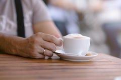 Mano de un hombre joven en una tabla de madera en el café Foto de archivo