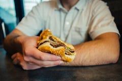 Mano de un hombre joven que sostiene una hamburguesa Fotos de archivo libres de regalías