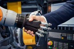 Mano de un hombre de negocios que sacude las manos con un robot de Android fotografía de archivo