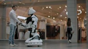 Mano de un hombre de negocios que sacude las manos con un robot de Android El concepto de interacci?n humana con inteligencia art metrajes