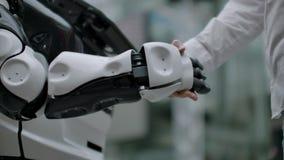 Mano de un hombre de negocios que sacude las manos con un robot de Android El concepto de interacci?n humana con inteligencia art almacen de metraje de vídeo