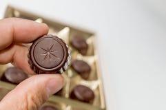 Mano de un hombre que sostiene un chocolate de una caja de chocolates fotos de archivo