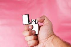 Mano de un hombre que sostiene el mechero contra rosa claro Fotos de archivo