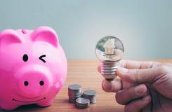 Mano de un hombre que sostiene una bombilla el dinero de los ahorros del planeamiento de las monedas para comprar un concepto cas imagen de archivo
