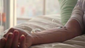 Mano de un paciente con el metro del pulso que miente con el contador del descenso en la cama 1920x1080 almacen de metraje de vídeo
