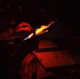 Mano de un vidrio de trabajo del ventilador de cristal sobre una llama abierta Imagen de archivo libre de regalías