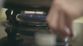 Mano de una iluminación de la persona encima de la estufa de gas almacen de metraje de vídeo