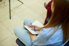 Mano de una muchacha con una pluma en una libreta blanca vacía fotografía de archivo