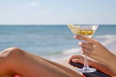 Mano de una muchacha con un cóctel en la playa Foto de archivo libre de regalías