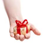 Mano de una muchacha con un regalo aislado en blanco Imagen de archivo libre de regalías
