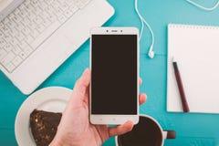 Mano de una muchacha con un teléfono, mesa con un ordenador portátil, espacio para el texto Fotos de archivo libres de regalías